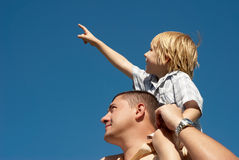 Younger brother. Younger on shoulders at senior brother against the sky stock image