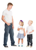Younger brother and sister look at older brother Royalty Free Stock Photography