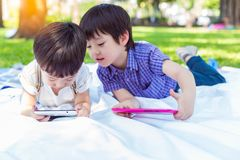 Younger brother watching movie or playing games on tablet and ignoring his older brother. Older brother peeking his little boy tha royalty free stock photo