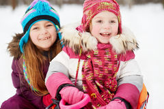 Younger girl sits in sled, older one sits behind her Stock Photos