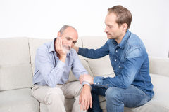 Younger man comforting older man Royalty Free Stock Photo