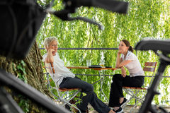 Younger and older business woman sitting in a beer garden Royalty Free Stock Photography