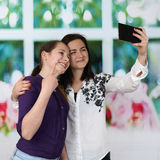 Younger and older girls in embrace make self shot using smartpho Royalty Free Stock Photos