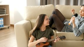 Younger and older sister singing in the living room. One is playing at the ukulele while the other is singing at a microfone on the couch stock footage