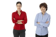 Younger and older woman standing arms crossed stock image