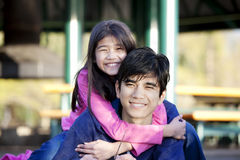 Younger sister hugging big brother. Younger sister hugging her big brother around the neck Royalty Free Stock Photos