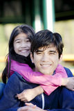Younger sister hugging big brother Stock Photography