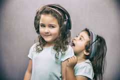Younger sister screaming at her older sister in headphones Royalty Free Stock Photos