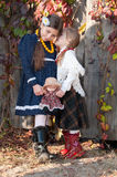 Younger sister whispers secrets older sister Royalty Free Stock Image