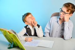 The younger student thinks about the task at school in class.  royalty free stock image