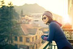 Younger traveling woman standing outside building terrace and lo. Oking to destination scene against beautiful sun rise stock images