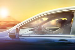 Younger woman driving passenger car in urban against sunset sky Stock Image