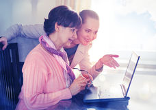 Younger woman helping an elderly person using laptop computer for internet search. Stock Photo