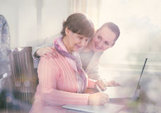 Younger woman helping an elderly person using laptop Stock Photos