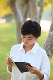 Younger woman  reading book in park Stock Photo