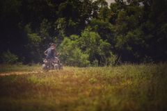 Younger woman riding on sport quad tv vehicle on country field Royalty Free Stock Photos
