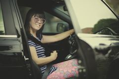 Younger woman sitting on driver seat of suv car and fasten seat Royalty Free Stock Images