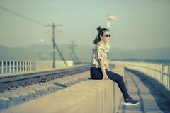 Younger woman wearing sun glasses sitting beside railway track. Younger woman wearing sun   glasses sitting beside railway track Royalty Free Stock Photography