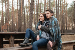 Youngers looking away while sitting on bench Royalty Free Stock Photos