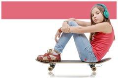 Younggirl bonito que presenta con un monopatín, asiento en patín Fotografía de archivo libre de regalías