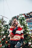 Younggirl on the red Square through winter holiday in Moscow, stylish and beautiful posing near to Christmas tree royalty free stock images