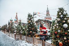 Younggirl on the red Square through winter holiday in Moscow, stylish and beautiful posing near to Christmas tree stock photo