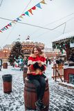 Younggirl on the red Square through winter holiday in Moscow, stylish and beautiful posing near to Christmas tree stock photos