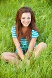 youngl женщины зеленого цвета травы сидя Стоковое фото RF