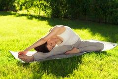Youngl kvinna som gör yoga i parkera i morgonen Arkivfoton