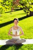 Youngl kvinna som gör yoga i parkera i morgonen Arkivbilder