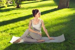 Youngl kvinna som gör yoga i parkera i morgonen Arkivbild