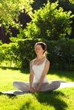 Youngl kvinna som gör yoga i parkera i morgonen Royaltyfri Foto