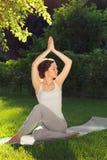 Youngl kvinna som gör yoga i parkera i morgonen Royaltyfria Bilder