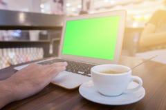 Youngman che lavora con il computer portatile in caffè, computer portatile con lo schermo verde Fotografia Stock Libera da Diritti