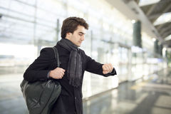 Youngman looking at watch at airport Royalty Free Stock Photography