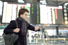 Youngman looking at watch at airport Stock Image