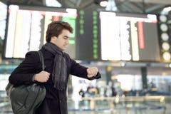 Youngman patrzeje zegarek przy lotniskiem obraz stock