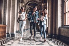 Youngs and beautiful. Group of confident students are walking in the college,chatting and smiling.  stock photos
