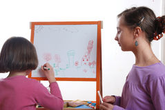 Youngs girls drawing. Young girls drawing on the white board stock image