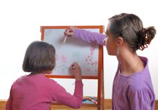 Youngs girls drawing on the white board. Two Youngs girls drawing on the white board stock photo