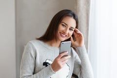 Youngsmilingsvrouw die aan haar vrienden op de telefoon babbelen en van haar dag thuis genieten Stock Foto's