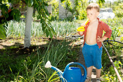 Youngster helping out in the veggie garden. Standing with a spade over his shoulder contemplating a blue plastic watering can Royalty Free Stock Photos