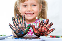 Youngster with painted hands at table. Royalty Free Stock Photography