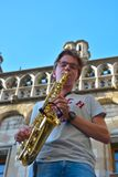 Youngster playing the sax. GHENT, BELGIUM, September 2016: streetartist playing the sax in front of a historic building Stock Photo