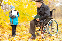 Youngster showing a disabled man a tablet-pc Royalty Free Stock Images