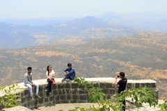 Youngsters sitting on walls of the fort for a photo at Sinhagad fort, Pune. Maharashtra, India stock image