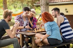 Youngsters thinks while playing chess. In nature Royalty Free Stock Image