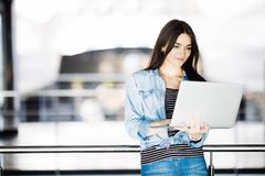 Youngwoman与她的在扶手栏杆的膝上型计算机一起使用 免版税库存图片