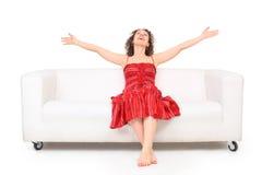 Youngwoman in vestito rosso si siede sul sofà Fotografie Stock Libere da Diritti