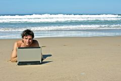 Younug gy working on the internet at the beach Royalty Free Stock Photo